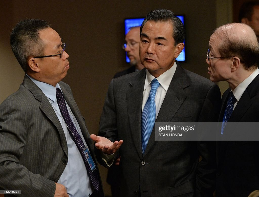 China's Foreign Minister Wang Yi (C) talks with aides outside the United Nations Security Council just after the Council voted to approve a resolution that will require Syria to give up its chemical weapons during a meeting September 27, 2013 at UN headquarters in New York. AFP PHOTO/Stan HONDA