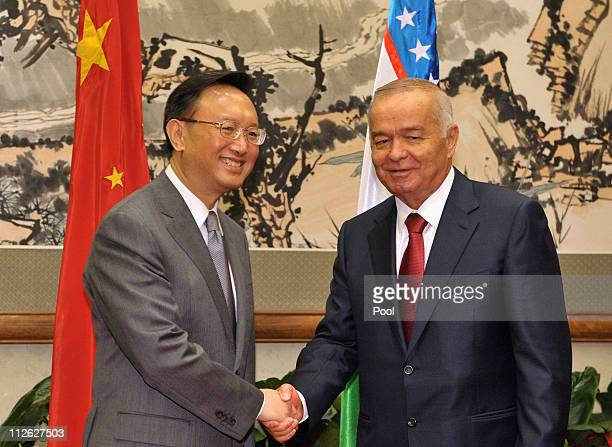 China's Foreign Minister Yang Jiechi shakes hands with Uzbekistan President Islam Karimov during their meeting at the Diaoyutai State Guesthouse on...