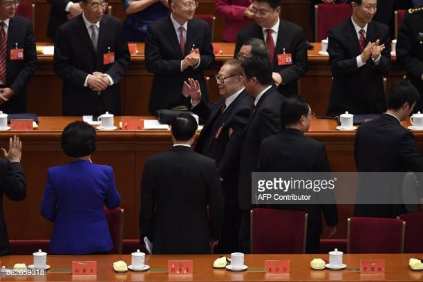 China's former president Chinese former president Jiang Zemin waves as he leaves at the opening session of the Chinese Communist Party's Congress at...