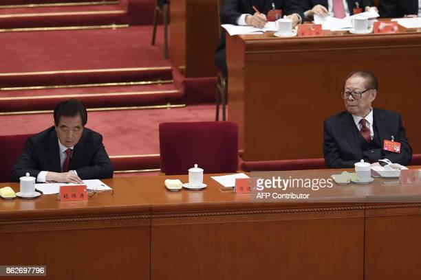 China's former president Jiang Zemin looks at former president Hu Jintao during the opening session of the Chinese Communist Party's Congress at the...