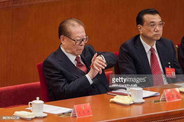China's former president Jiang Zemin looks at the time on his watch as he listens to Chinese President Xi Jinping's address while sitting next to...