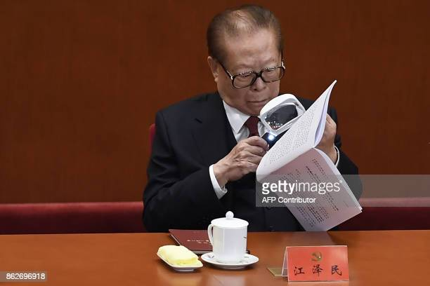 China's former president Jiang Zemin reads the script of a speech as he attends the opening session of the Chinese Communist Party's Congress at the...