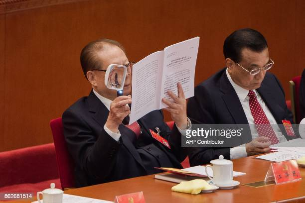 China's former president Jiang Zemin reads Xi speech with a magnifying glass as he listens to President Xi Jinping's address while sitting next to...