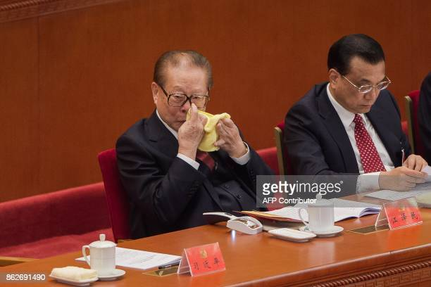 China's former president Jiang Zemin uses a tissue to clear his nose as he listens to President Xi Jinping's address while sitting next to Premier Li...