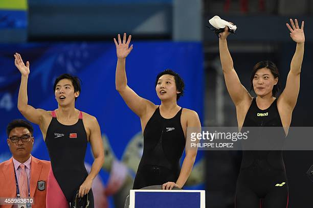 China's Guo Junjun Cao Yue and Tang Yi cheer on final lap swimmer Shen Duo during their victory in the final for the women's 4 x 200m freestyle relay...