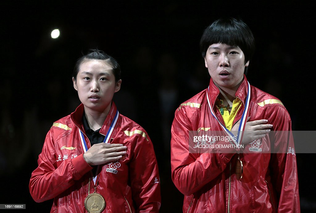 China's Guo Yue (L) and Li Xiaoxia sing their national anthem on May 20, 2013 in Paris, during the Women's Doubles ceremony of the World Table Tennis Championships. AFP PHOTO / JACQUES DEMARTHON