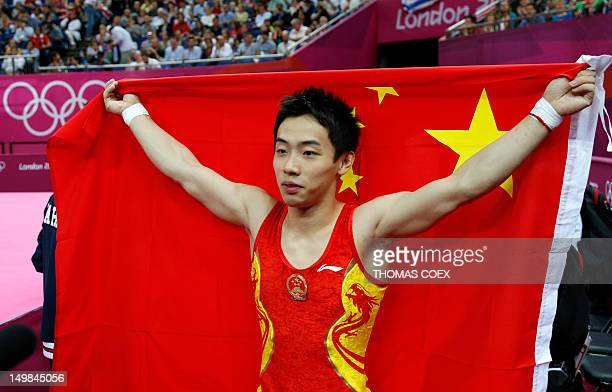 China's gymnast Zou Kai celebrates with his national flag after winning the men's floor exercise final of the artistic gymnastics event of the London...