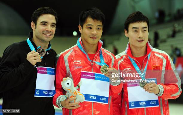 China's He Chong celebrates with his gold medal Silver medalist China's Qin Kai and Bronze medalist Canada's Alexandre Despatie following their Men's...