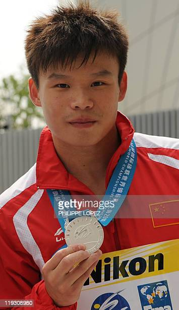 China's He Min poses with his silver medal after the award ceremony for the final of the men's 1metre springboard diving event in the FINA World...