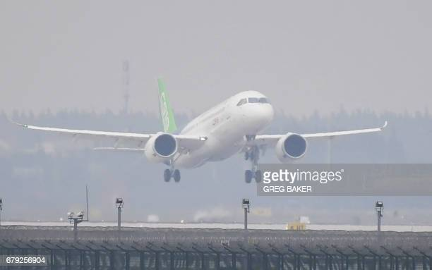 China's homegrown C919 passenger jet takes off from Pudong International Airport on its maiden flight in Shanghai on May 5 2017 The first large...
