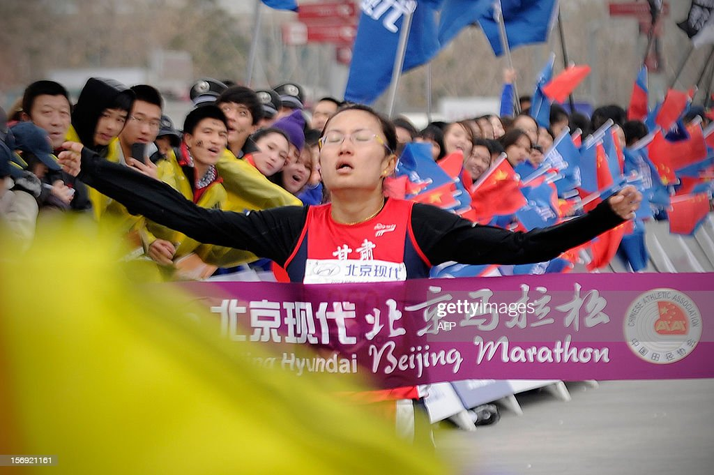 China's Jia Chaofeng crosses the finishing line to win the women's portion of the Beijing Marathon in the Chinese capital on November 25, 2012. A total of 30,000 runners took part in the race. AFP PHOTO / WANG ZHAO
