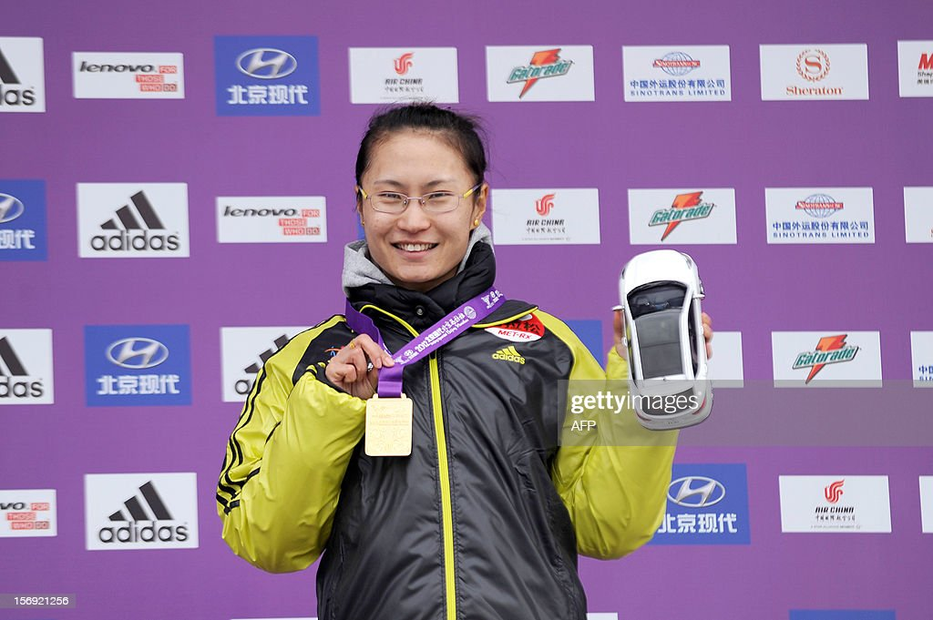 China's Jia Chaofeng poses with her medal on the podium as she attends the presentation ceremony after winning the woman's portion of the Beijing Marathon in the Chinese capital on November 25, 2012. A total of 30,000 runners took part in the race.