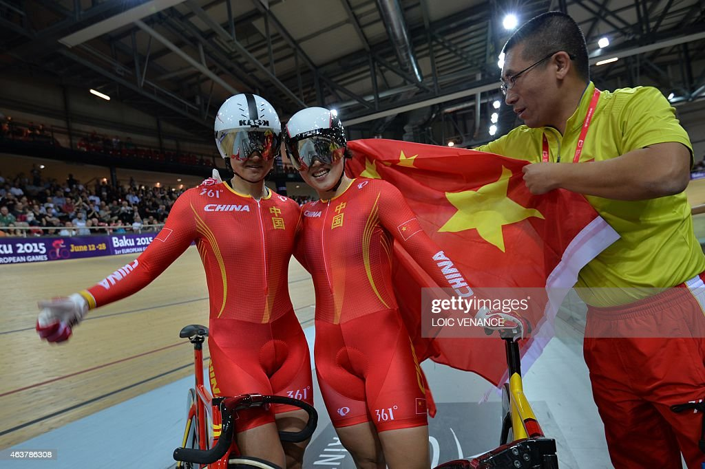 China's Jinjie Gong (R) and Tianshi Zhong celebrate after coming in first and setting a new world record in the Women's Team Sprint finals at the UCI Track Cycling World Championships in Saint-Quentin-en-Yvelines, near Paris, on February 18, 2015. AFP PHOTO / LOIC VENANCE