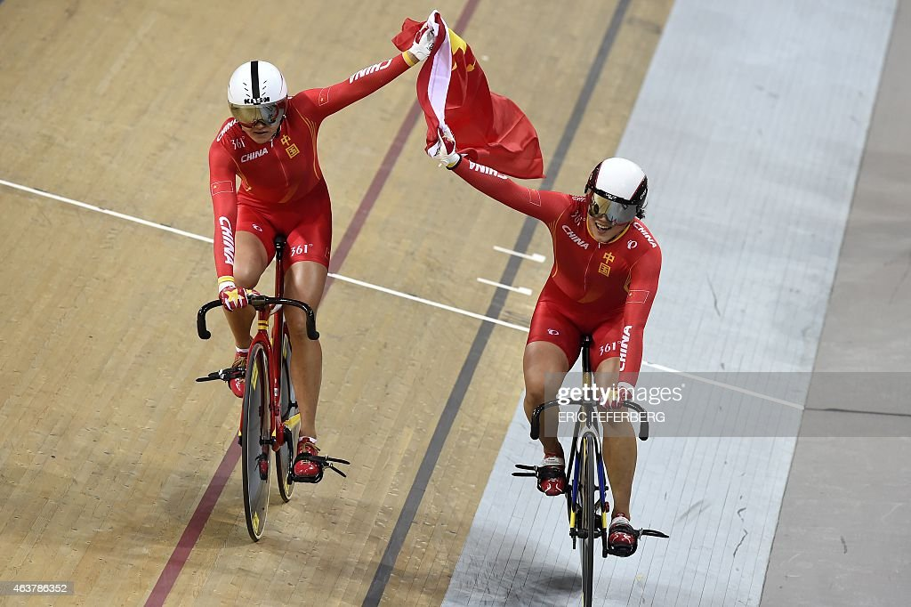 China's Jinjie Gong (R) and Tianshi Zhong celebrate after coming in first and setting a new world record in the Women's Team Sprint finals at the UCI Track Cycling World Championships in Saint-Quentin-en-Yvelines, near Paris, on February 18, 2015. AFP PHOTO / ERIC FEFERBERG