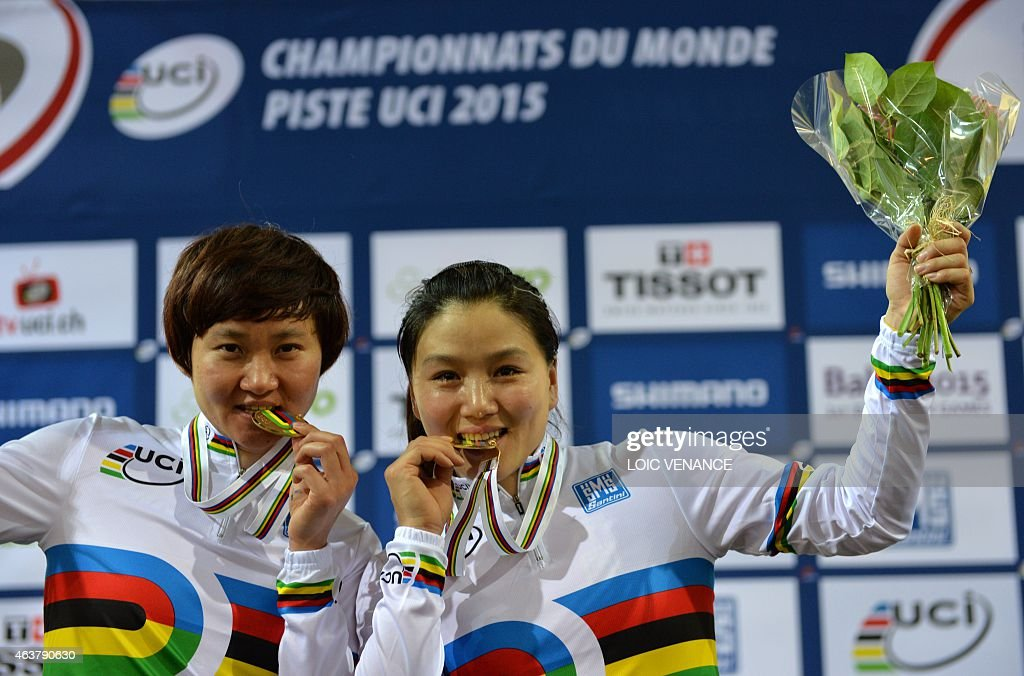 China's Jinjie Gong (R) and Tianshi Zhong celebrate on the podium after coming in first and setting a new world record in the Women's Team Sprint event at the UCI Track Cycling World Championships in Saint-Quentin-en-Yvelines, near Paris, on February 18, 2015. AFP PHOTO / LOIC VENANCE