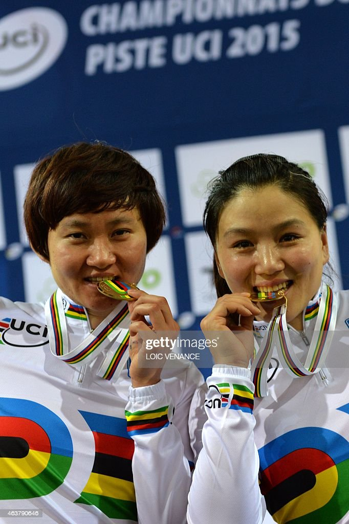 China's Jinjie Gong (R) and Tianshi Zhong celebrate on the podium after coming in first and setting a new world record in the Women's Team Sprint event at the UCI Track Cycling World Championships in Saint-Quentin-en-Yvelines, near Paris, on February 18, 2015.