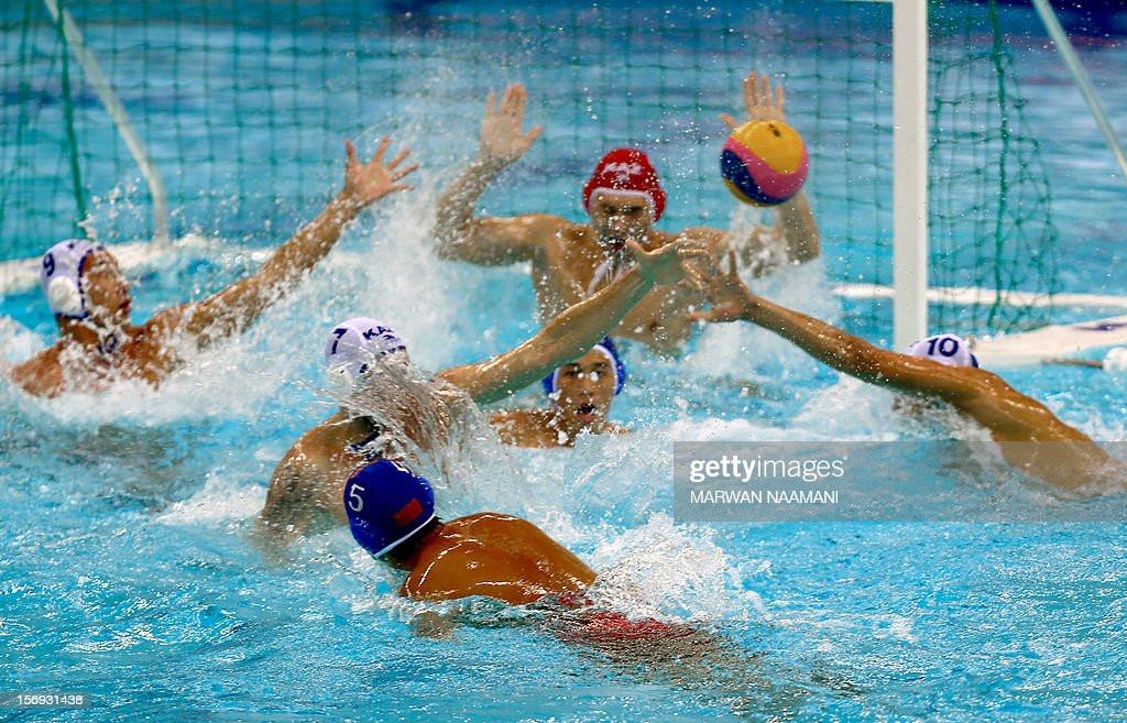 China's Junliang Guo (L) attempts to score against Kazakhstan in the final of the men's water polo championship at the 9th Asian Swimming Championships in Dubai, on November 25, 2012. China won 4-2 in a penalty shoot-out after a 9-9 draw at the final whistle.