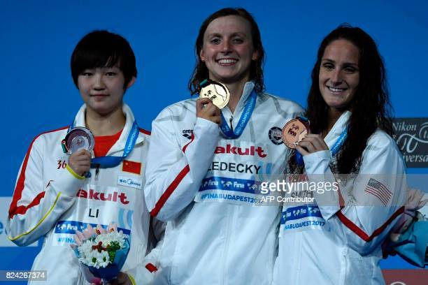 China's Li Bingjie US Katie Ledecky and US Leah Smith celebrate on the podium after the women's 800m freestyle final during the swimming competition...