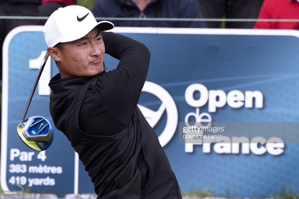 China's Li Haotong plays off the 1st tee during the first round of the 100th French Golf Open on July 30, 2016 at Le Golf National in Guyancourt, near Paris. / AFP / DOMINIQUE