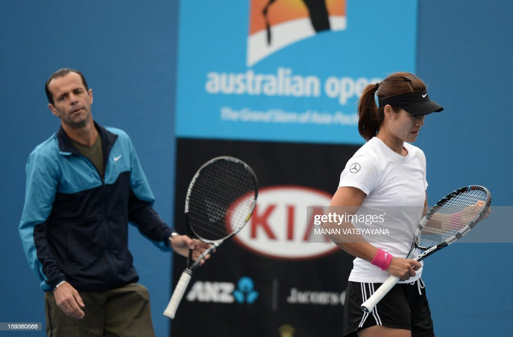 China's Li Na gestures as her coach Carlos Rodriguez looks on during a practice session ahead of the 2013 Australian Open tennis tournament on...