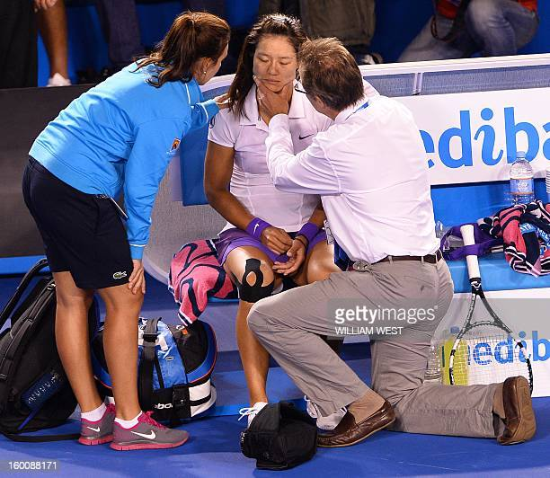 China's Li Na is treated by officials after falling during the women's singles final against Belarus's Victoria Azarenka on day 13 of the Australian...