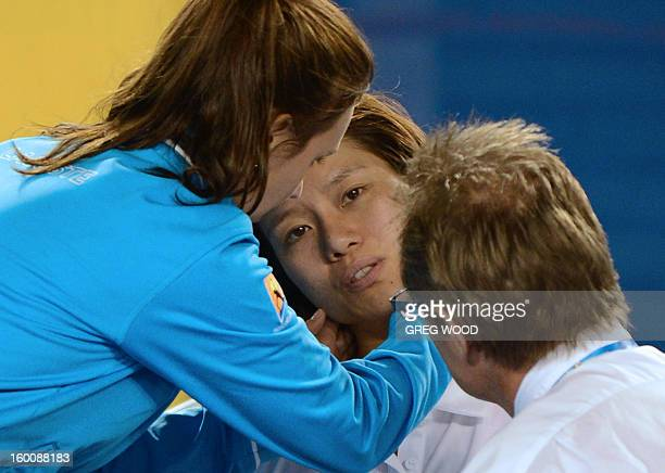 China's Li Na receives medical attention after falling during her women's singles final against Belarus's Victoria Azarenka on day thirteen of the...