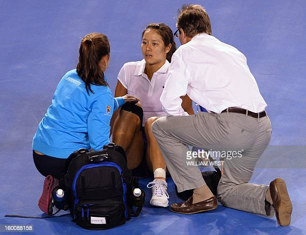 China's Li Na speaks with officials after falling during the women's singles final against Belarus's Victoria Azarenka on day 13 of the Australian...