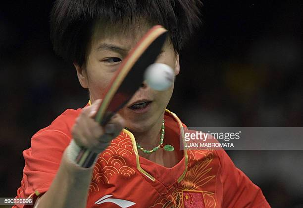 China's Li Xiaoxia hits a shot in the women's team gold medal final table tennis match against Germany at the Riocentro venue during the Rio 2016...