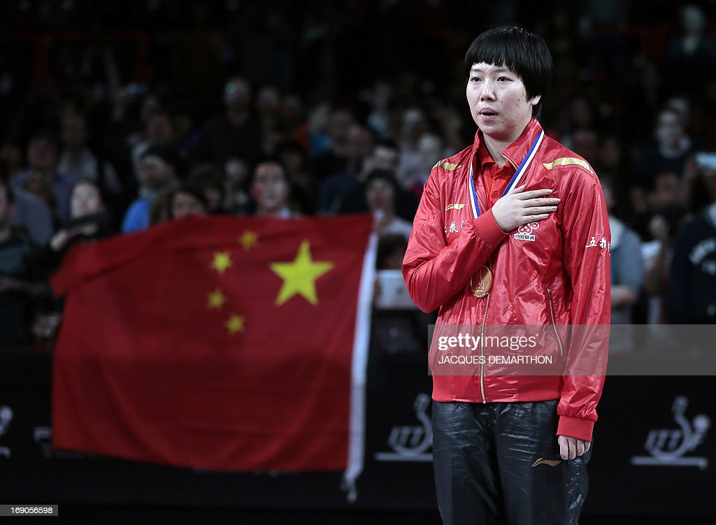 China's Li Xiaoxia listens her national anthem, on May 19, 2013 in Paris, during the trophy ceremony of the Women's Singles of the World Table Tennis Championships. AFP PHOTO / JACQUES DEMARTHON