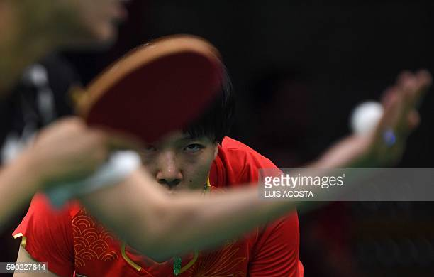 China's Li Xiaoxia waits for a serve in the women's team gold medal final table tennis match against Germany's Han Ying at the Riocentro venue during...