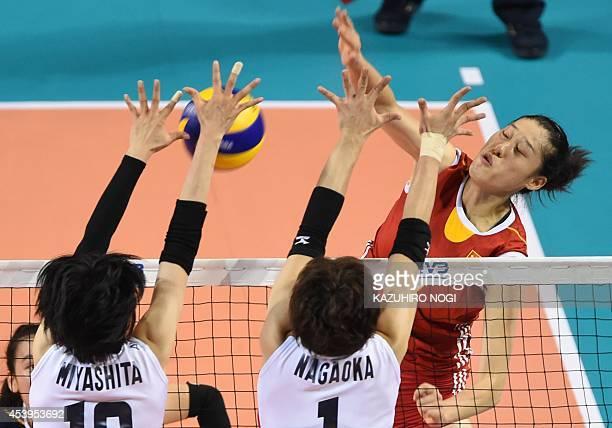 China's Liu Xiaotong is blocked her spike by Japan's Haruka Miyashita and Miyu Nagaoka during their volleyball match of the FIVB Women's World Grand...