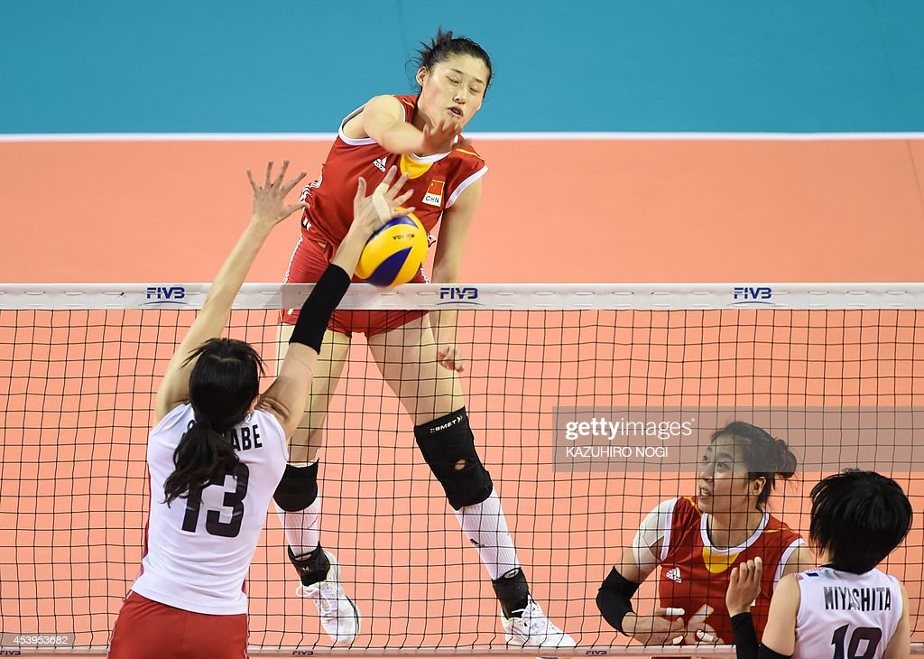 China's Liu Xiaotong (C) spikes the ball past Japan's Risa Shinnabe (L, #13) during their volleyball match of the FIVB Women's World Grand Prix finals in Tokyo on August 22, 2014.