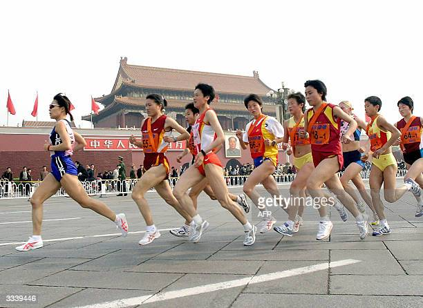 China's long distance runner Sun Yingjie keeps pace at the start of the Beijing International Marathon relay race as the runners pass the Tiananmen...