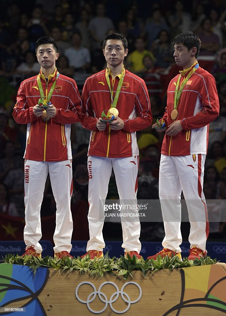 China's Ma Long, China's Xu Xin, and China's Zhang Jike pose with their gold medals after the final men's team table tennis match at the Riocentro venue during the Rio 2016 Olympic Games in Rio de Janeiro on August 17, 2016. / AFP / Juan Mabromata