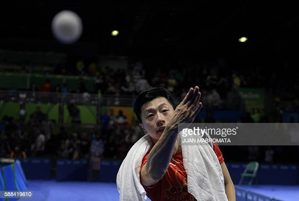 TOPSHOT China's Ma Long throws a ball into the crowd after beating Japan's Jun Mizutani in their men's singles semifinal table tennis match at the...