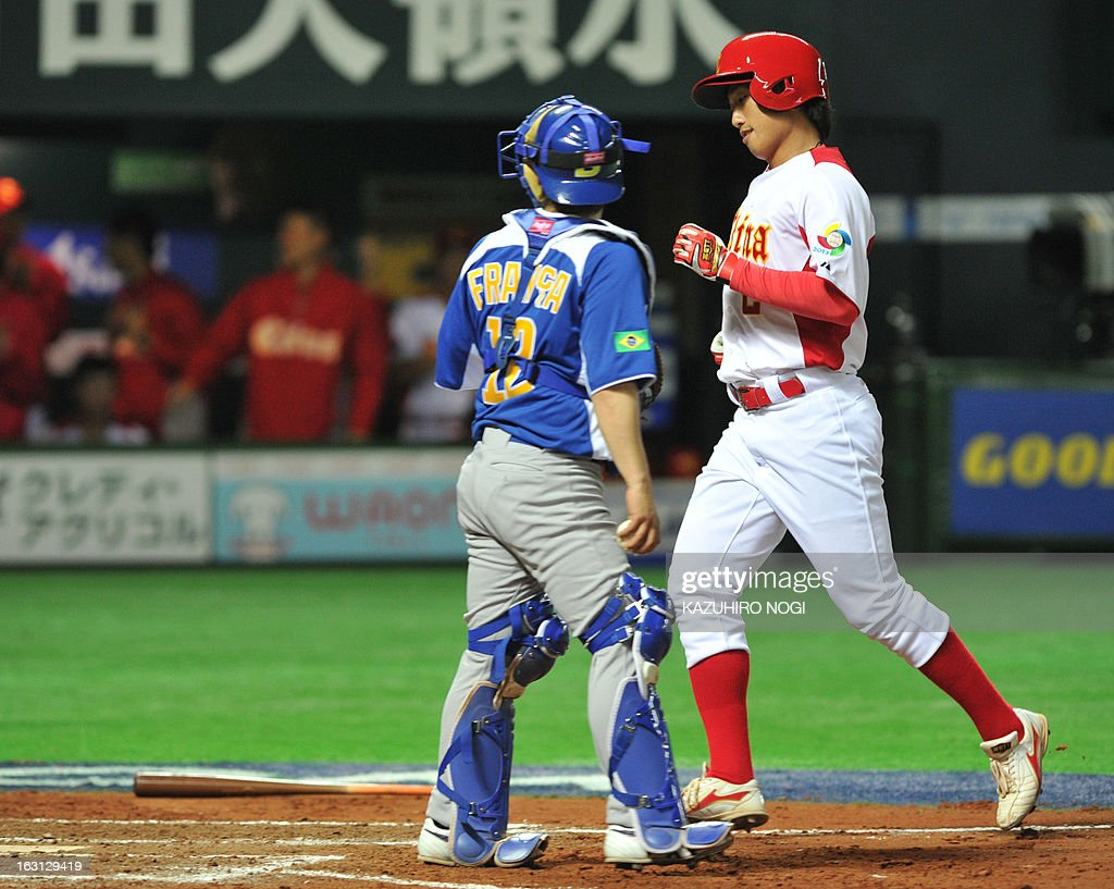 China's Meng Weiqiang (R) scores at home-plate as Brazil's catcher Diego Franca (L) looks on following a bases-loaded walk by pitcher Thyago Vieira during the eighth inning of their first-round Pool A game in the World Baseball Classic tournament in Fukuoka on March 5, 2013. China beat Brazil 5-2. AFP PHOTO / KAZUHIRO NOGI