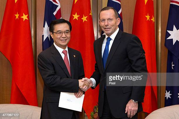 China's Minister of Commerce Gao Hucheng shakes hands with Australian Prime Minister Tony Abbott at Parliament House on June 17 2015 in Canberra...