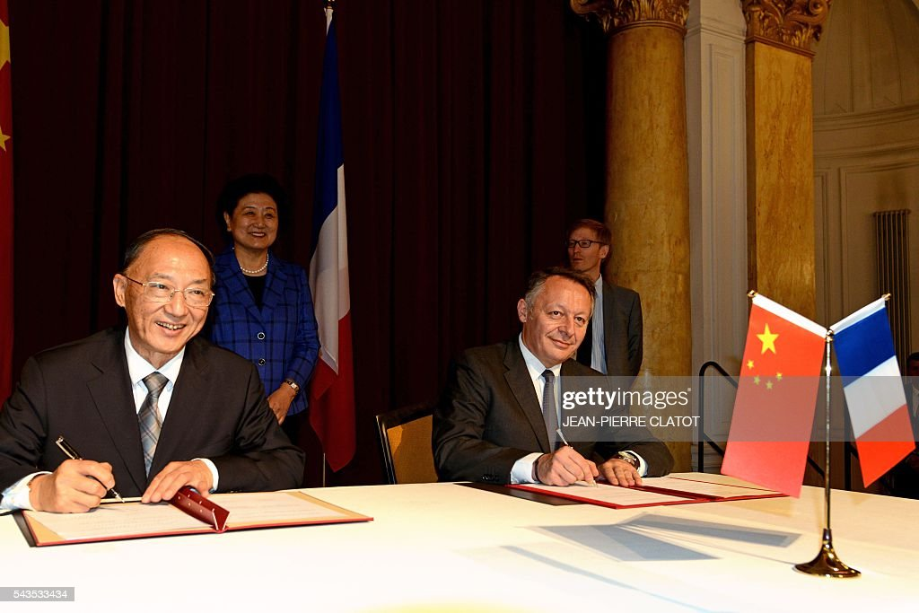 China's Minister of the General Administration of Sport, Liu Peng (L) and French Minister for Sports Thierry Braillard (R) sign on June 29, 2016 a cooperation agreement on winter sports, as China's Vice Premier, Liu Yandong (Rear L0 looks on, during a ceremony in Chamonix Mont-Blanc, French Alps. / AFP / JEAN