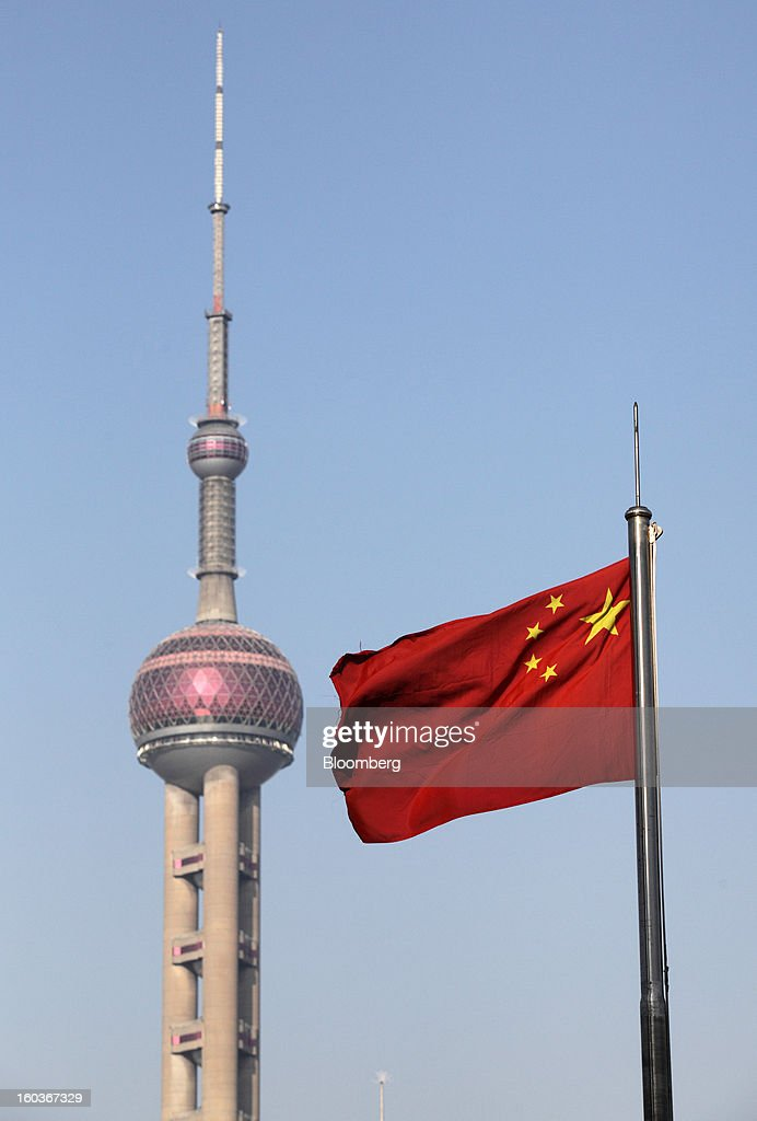 China's national flag flies as the Oriental Pearl Tower stands in Shanghai, China, on Monday, Jan. 28, 2013. China's economic growth accelerated for the first time in two years as government efforts to revive demand drove a rebound in industrial output, retail sales and the housing market. Photographer: Tomohiro Ohsumi/Bloomberg via Getty Images