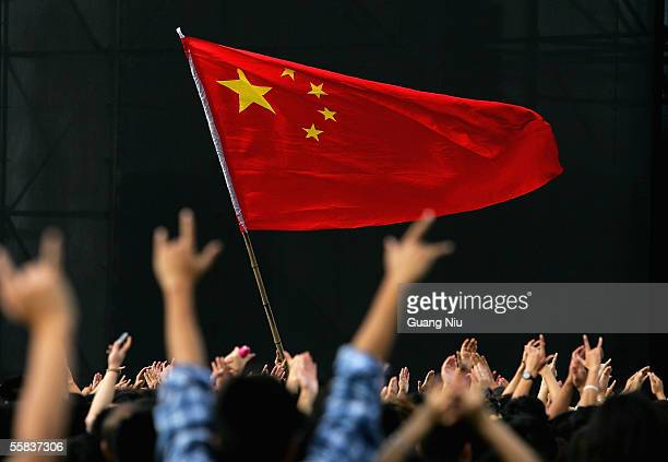 Chinas national flag is flown during a rockandroll festival to mark Chinese National Day on October 2 2005 in Beijing China Various activities are...