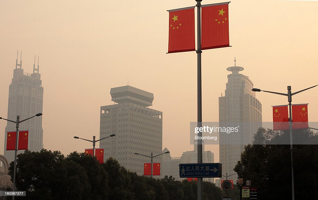 China's national flags are displayed along a street as commercial buildings stand in the distance in Shanghai, China, on Tuesday, Jan. 29, 2013. China's economic growth accelerated for the first time in two years as government efforts to revive demand drove a rebound in industrial output, retail sales and the housing market. Photographer: Tomohiro Ohsumi/Bloomberg via Getty Images