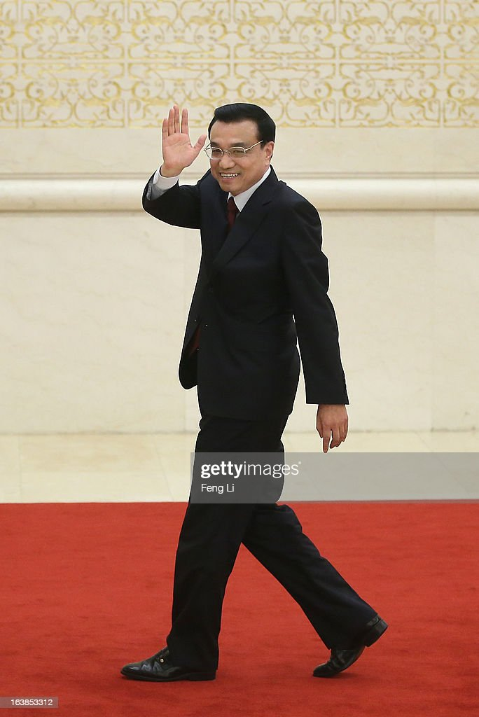 China's newly elected Premier Li Keqiang waves as he leaves a news conference after the closing session of the National People's Congress (NPC) at the Great Hall of the People on March 17, 2013 in Beijing, China. Chinese Premier Li Keqiang has vowed to tackle with mounting problems of environment pollution and food safety on Sunday.