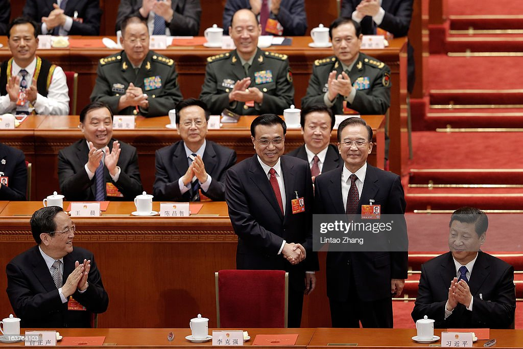 China's newly-elected Premier <a gi-track='captionPersonalityLinkClicked' href=/galleries/search?phrase=Li+Keqiang&family=editorial&specificpeople=2481781 ng-click='$event.stopPropagation()'>Li Keqiang</a> (Fort 2nd-L) shakes hands with former Chinese Premier <a gi-track='captionPersonalityLinkClicked' href=/galleries/search?phrase=Wen+Jiabao&family=editorial&specificpeople=204598 ng-click='$event.stopPropagation()'>Wen Jiabao</a> (fort 2nd-R) near Chinese President <a gi-track='captionPersonalityLinkClicked' href=/galleries/search?phrase=Xi+Jinping&family=editorial&specificpeople=2598986 ng-click='$event.stopPropagation()'>Xi Jinping</a> (R) during the fifth plenary meeting of the National People's Congress at the Great Hall of the People on March 15, 2013 in Beijing, China. <a gi-track='captionPersonalityLinkClicked' href=/galleries/search?phrase=Li+Keqiang&family=editorial&specificpeople=2481781 ng-click='$event.stopPropagation()'>Li Keqiang</a> was elected as China's Premier Friday at the 12th National People's Congress, the country's top legislature.