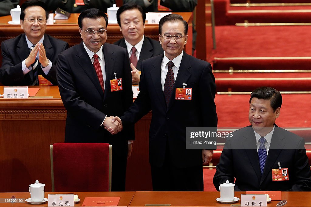 China's newly-elected Premier <a gi-track='captionPersonalityLinkClicked' href=/galleries/search?phrase=Li+Keqiang&family=editorial&specificpeople=2481781 ng-click='$event.stopPropagation()'>Li Keqiang</a> (L) shakes hands with former Chinese Premier <a gi-track='captionPersonalityLinkClicked' href=/galleries/search?phrase=Wen+Jiabao&family=editorial&specificpeople=204598 ng-click='$event.stopPropagation()'>Wen Jiabao</a> near Chinese President <a gi-track='captionPersonalityLinkClicked' href=/galleries/search?phrase=Xi+Jinping&family=editorial&specificpeople=2598986 ng-click='$event.stopPropagation()'>Xi Jinping</a> (R) during the fifth plenary meeting of the National People's Congress at the Great Hall of the People on March 15, 2013 in Beijing, China.<a gi-track='captionPersonalityLinkClicked' href=/galleries/search?phrase=Li+Keqiang&family=editorial&specificpeople=2481781 ng-click='$event.stopPropagation()'>Li Keqiang</a> was elected as China's Premier Friday at the 12th National People's Congress, the country's top legislature.