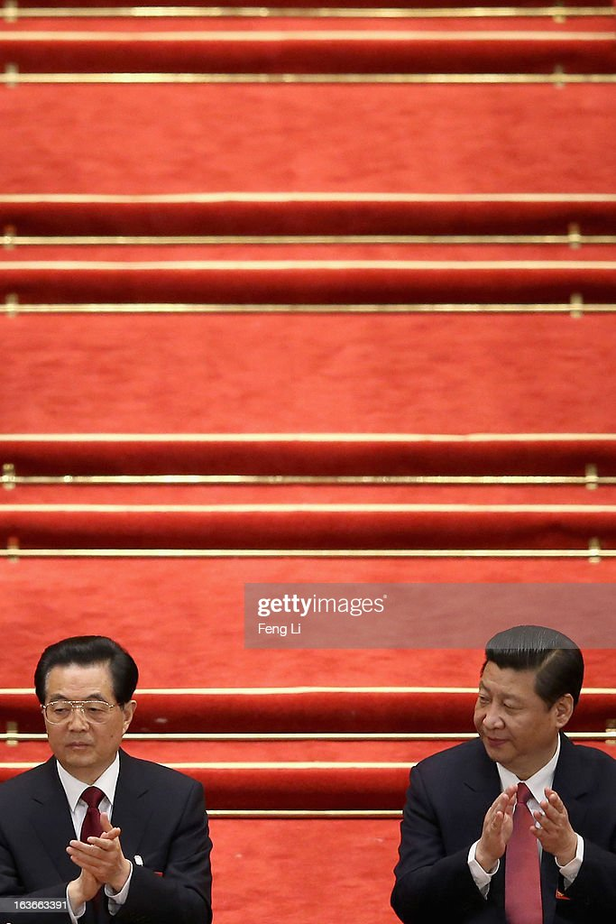 China's newly-elected President Xi Jinping (R) and former President Hu Jintao (L) attend the fourth plenary meeting of the National People's Congress at the Great Hall of the People on March 14, 2013 in Beijing, China. Xi Jinping, general secretary of the Communist Party of China Central Committee, was elected President of the People's Republic of China and Chairman of the Central Military Commission on Thursday.