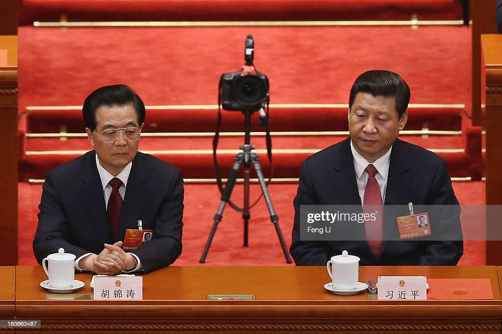 China's newly-elected President Xi Jinping (R) and former President Hu Jintao (L) sit as a remote camera placed behind them during the fourth plenary meeting of the National People's Congress at the Great Hall of the People on March 14, 2013 in Beijing, China. Xi Jinping, general secretary of the Communist Party of China Central Committee, was elected President of the People's Republic of China and Chairman of the Central Military Commission on Thursday.