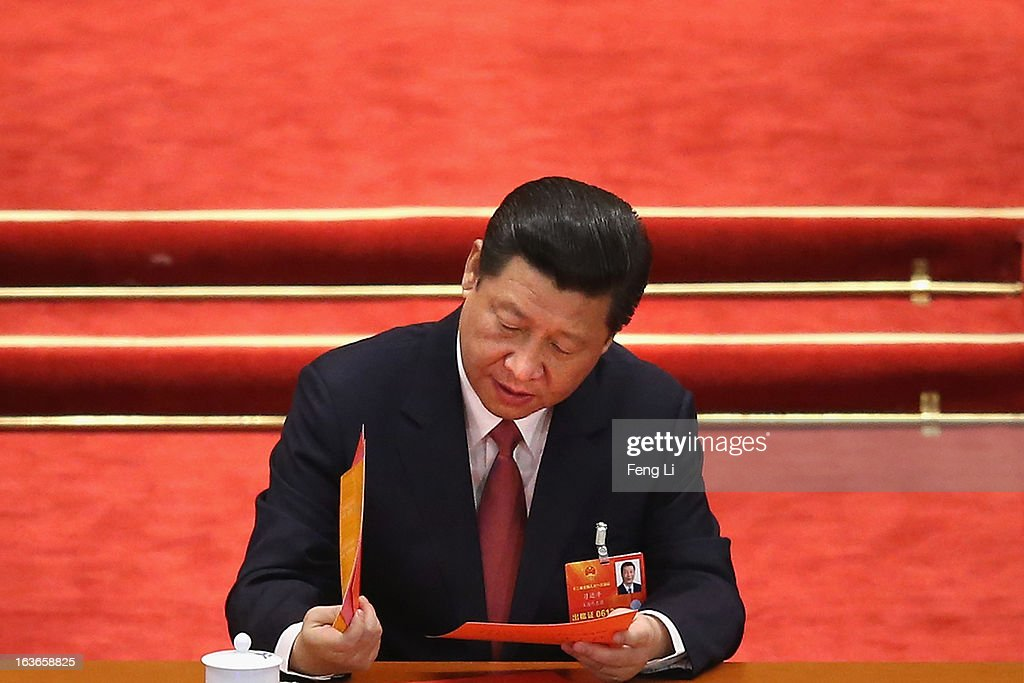 China's newly-elected President Xi Jinping reads his ballot papers prior to the election for a new president of China during the fourth plenary meeting of the National People's Congress (NPC) at the Great Hall of the People on March 14, 2013 in Beijing, China. Xi Jinping, general secretary of the Communist Party of China Central Committee, was elected President of the People's Republic of China and Chairman of the Central Military Commission on Thursday.