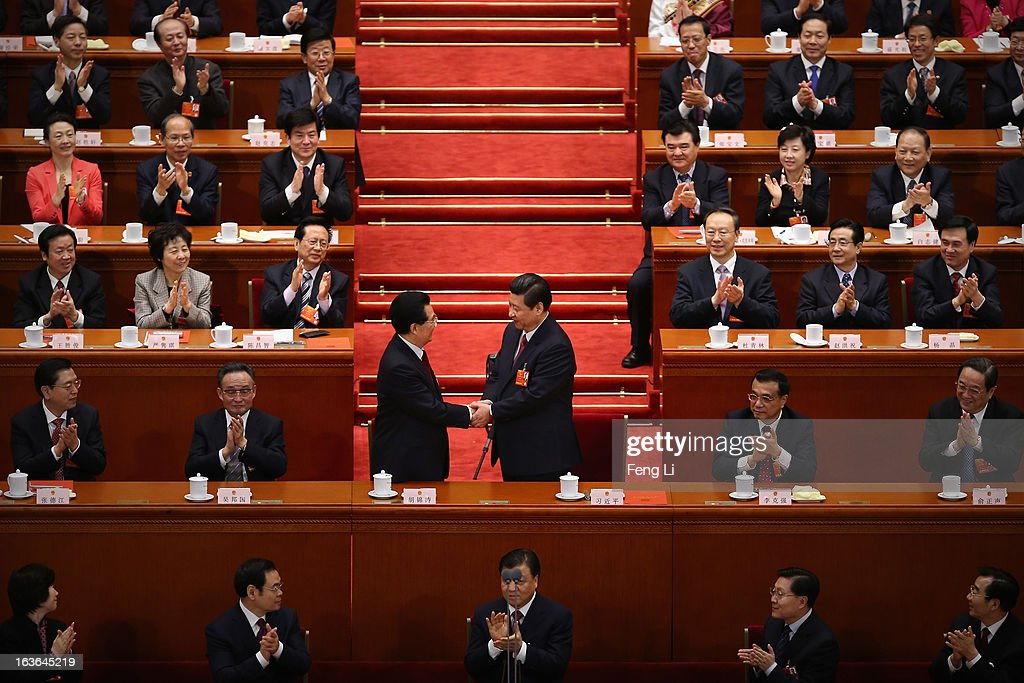 China's newly-elected President <a gi-track='captionPersonalityLinkClicked' href=/galleries/search?phrase=Xi+Jinping&family=editorial&specificpeople=2598986 ng-click='$event.stopPropagation()'>Xi Jinping</a> (R) shakes hands with former President Hu Jintao (L) as other delegates clap during the fourth plenary meeting of the National People's Congress (NPC) at the Great Hall of the People on March 14, 2013 in Beijing, China. <a gi-track='captionPersonalityLinkClicked' href=/galleries/search?phrase=Xi+Jinping&family=editorial&specificpeople=2598986 ng-click='$event.stopPropagation()'>Xi Jinping</a>, general secretary of the Communist Party of China Central Committee, was elected President of the People's Republic of China and Chairman of the Central Military Commission on Thursday.