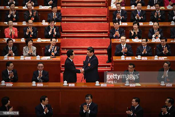 China's newlyelected President Xi Jinping shakes hands with former President Hu Jintao as other delegates clap during the fourth plenary meeting of...