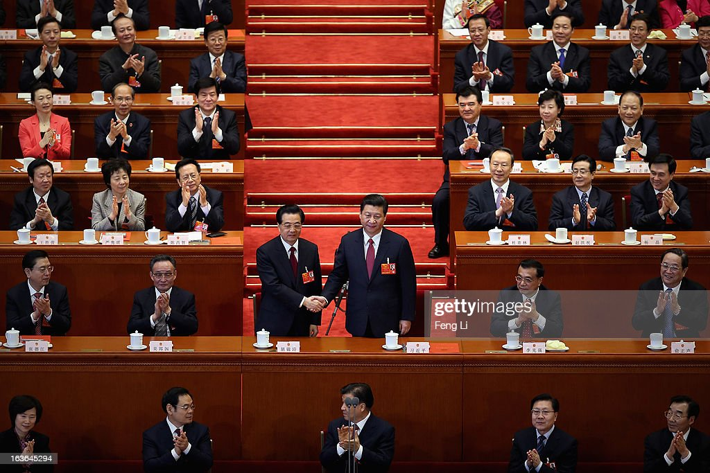 China's newly-elected President <a gi-track='captionPersonalityLinkClicked' href=/galleries/search?phrase=Xi+Jinping&family=editorial&specificpeople=2598986 ng-click='$event.stopPropagation()'>Xi Jinping</a> (R) shakes hands with former President <a gi-track='captionPersonalityLinkClicked' href=/galleries/search?phrase=Hu+Jintao&family=editorial&specificpeople=203109 ng-click='$event.stopPropagation()'>Hu Jintao</a> (L) as other delegates clap during the fourth plenary meeting of the National People's Congress (NPC) at the Great Hall of the People on March 14, 2013 in Beijing, China. <a gi-track='captionPersonalityLinkClicked' href=/galleries/search?phrase=Xi+Jinping&family=editorial&specificpeople=2598986 ng-click='$event.stopPropagation()'>Xi Jinping</a>, general secretary of the Communist Party of China Central Committee, was elected President of the People's Republic of China and Chairman of the Central Military Commission on Thursday.